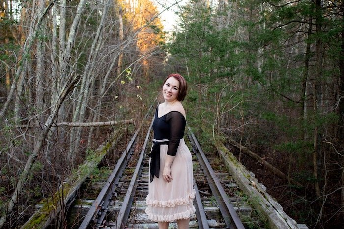 Lesleigh posing for a picture on train tracks.