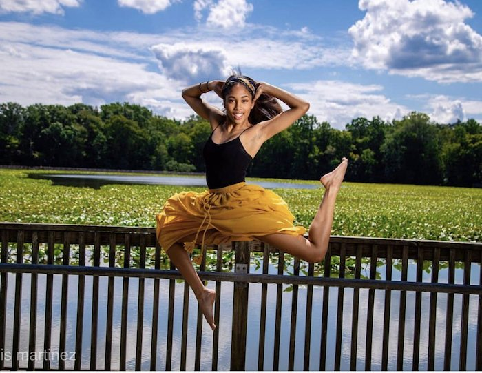 Brooke posing for a picture on a railing while wearing a yellow skirt with a lake in the background.