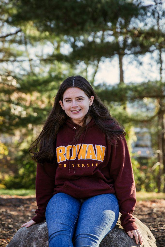 Sarah sitting on a rock outside in a Rowan sweatshirt.