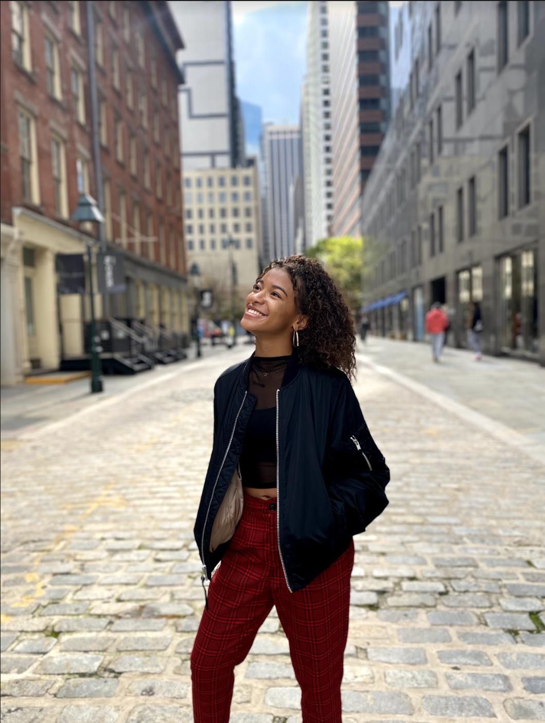 Gabrielle smiling on a cobblestone street.