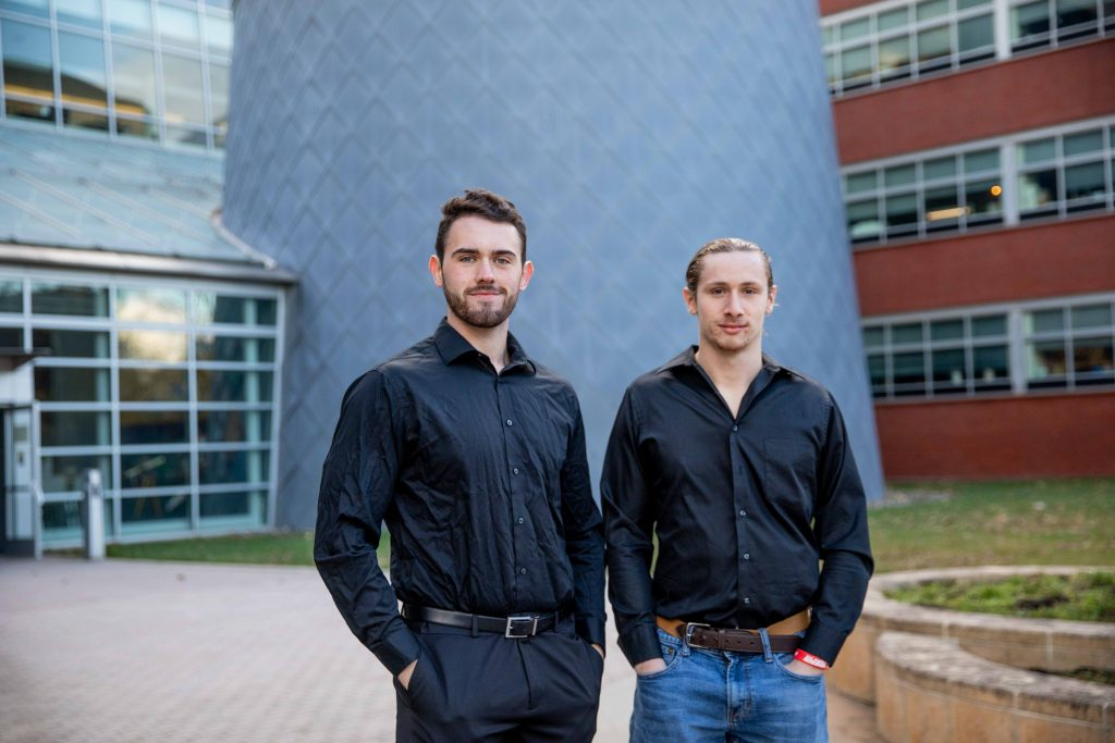Tom and his friend standing outside of Science Hall, both wearing black shirts and with their hands tucked in their pockets.