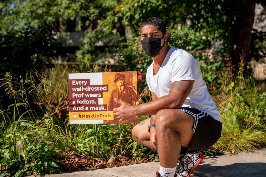 Trevor kneeling down in front of a sign with a mask on.