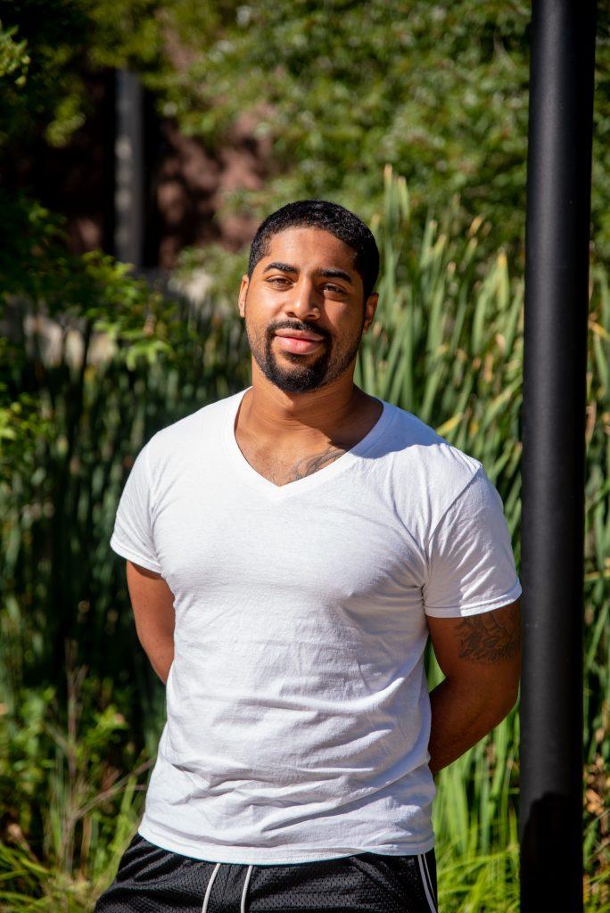 Trevor standing outside in a white shirt.