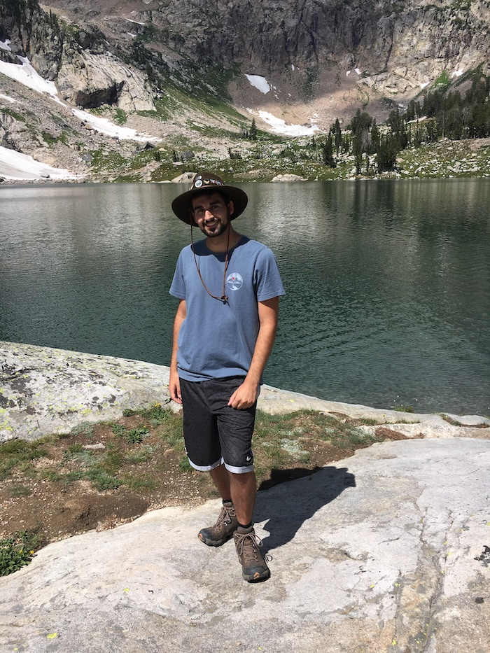 Matthew smiling and standing in front of a lake while wearing hiking gear.