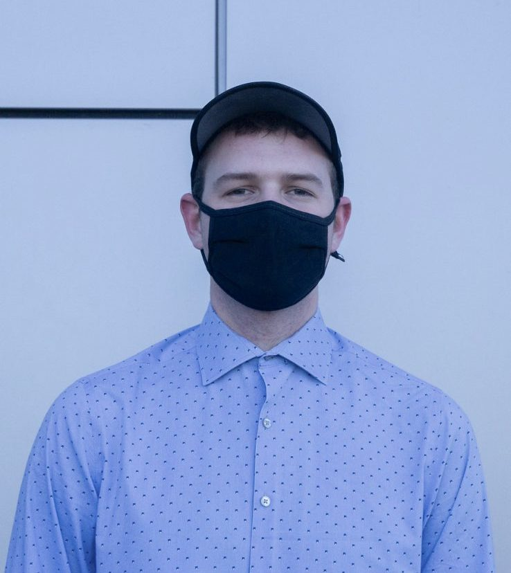 Joseph Laggy stands for a portrait while wearing a blue collared shirt and a black mask for covid.