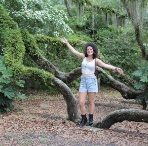 Brianna stands arms outstretched mimicking the tree branches behind her.