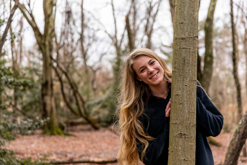 Ashleigh poses outdoors in a wooded area.