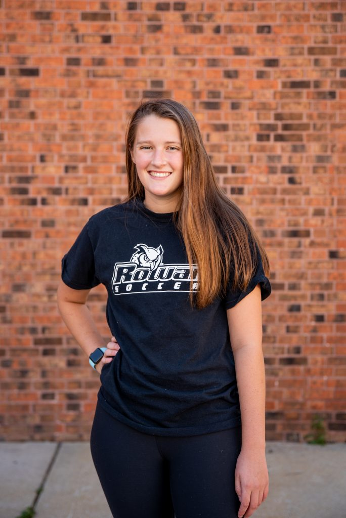 Catie poses in front of a brick wall wearing a Rowan soccer shirt.