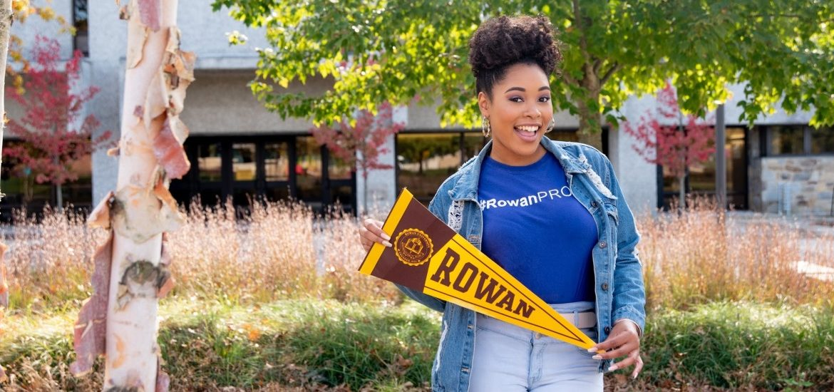 Cheyenne holds a pennant on campus.