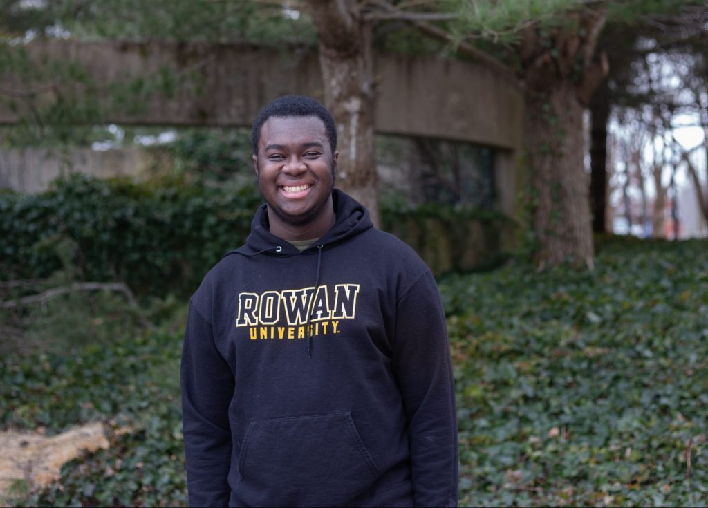 Gregory poses outside the student center in a Rowan sweatshirt.