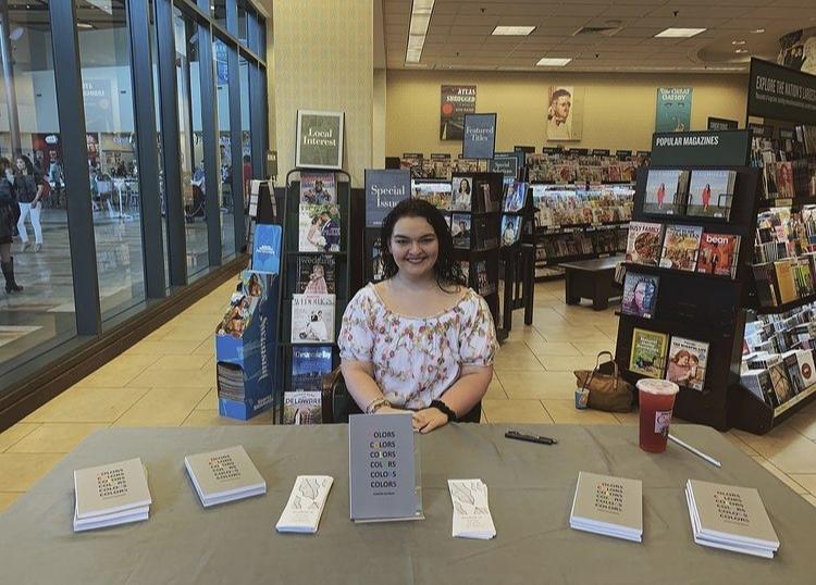 Jennifer poses at a book signing at a book store.