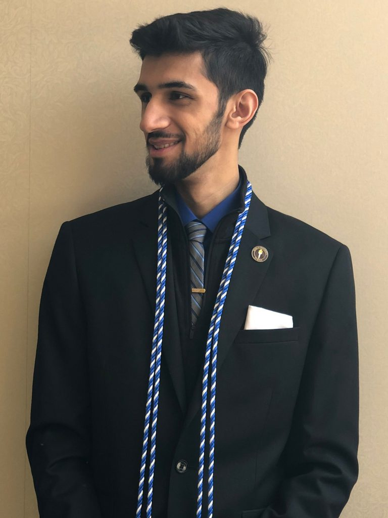 Fahed poses in a suit with his cords.
