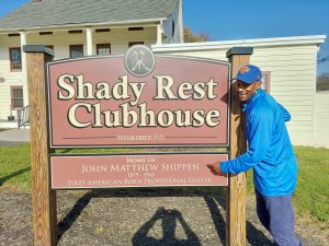 Brad posing with the Shady Rest Clubhouse sign and pointing to the name 'John Matthe Shippen'.