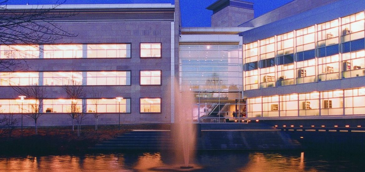 Rowan Hall in the College of Engineering at night, with fountains in the front.