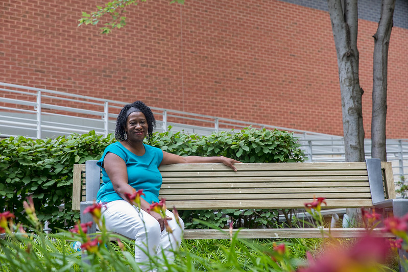 Michelle sits on a bench outside Cooper Hospital.