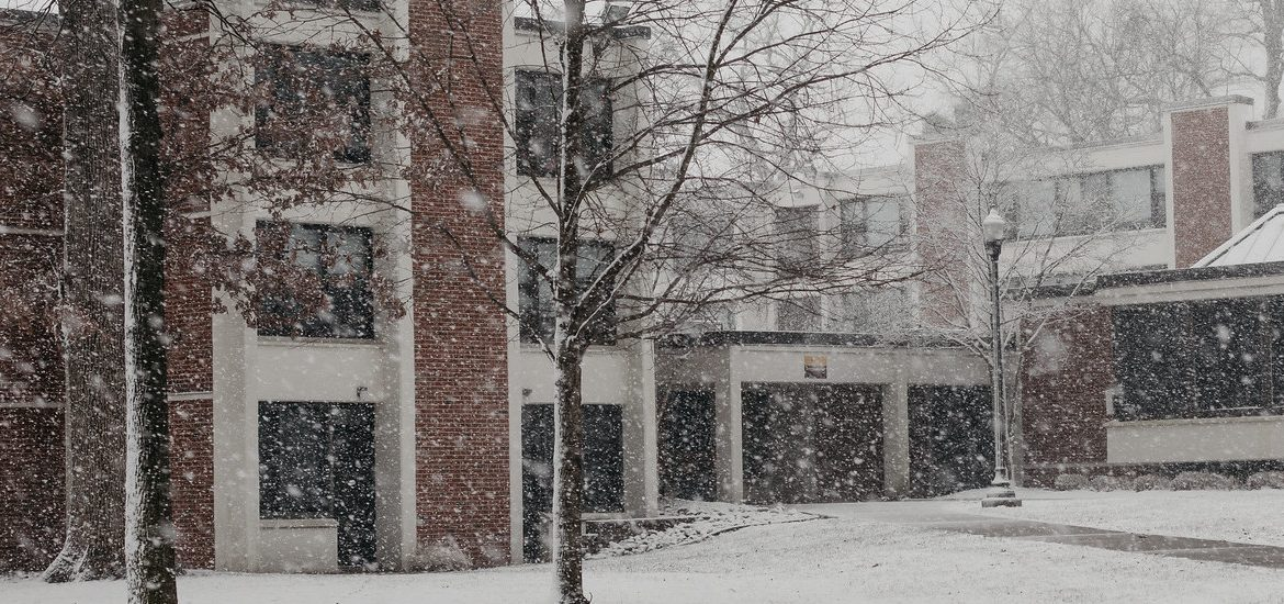 Exterior shot of falling snow outside a residence hall.