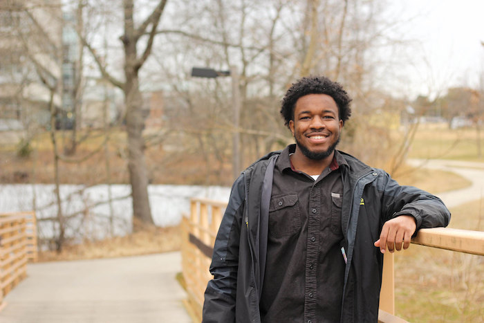 Akil leaning against the bridge and smiling outside Engineering Hall.