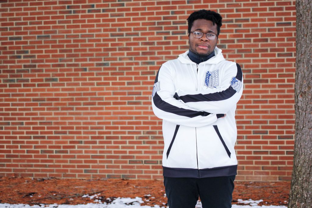 Ugonna poses in front of a brick wall.