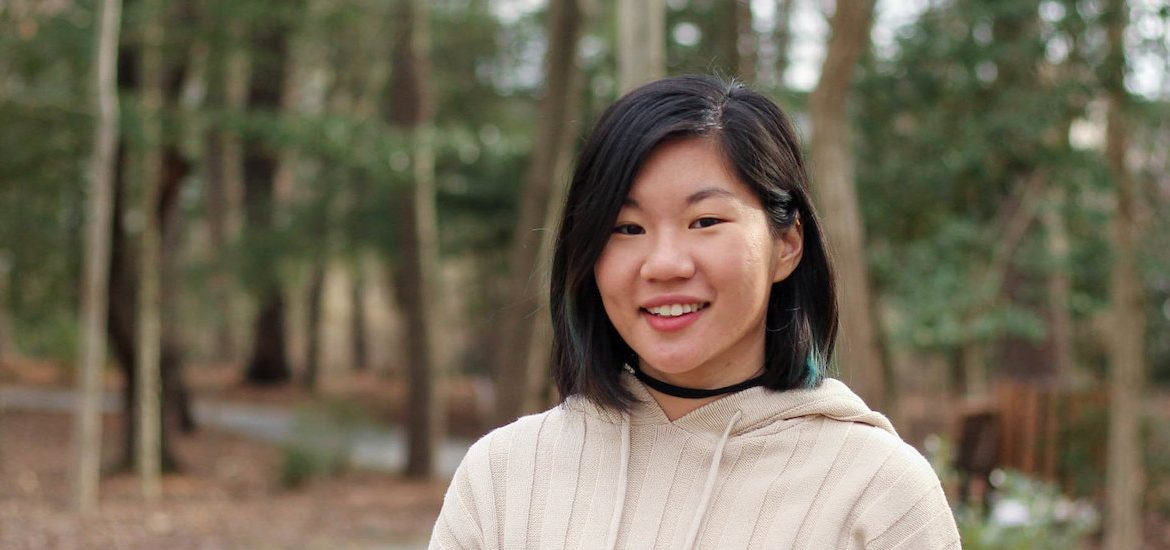 Jean stands outside in front of a wooded area on campus.