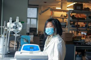 Jean wearing a lab coat and a blue mask while working in the lab.