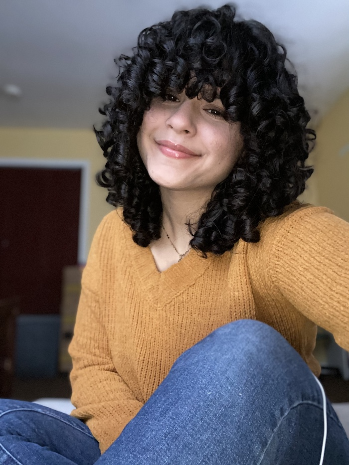 Amy smiling and posing for a selfie wearing a tan sweater and jeans.