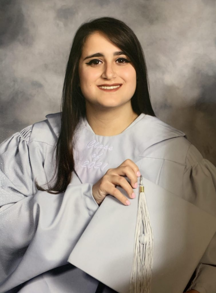 Kristina poses against a backdrop in her graduation cap and gown.