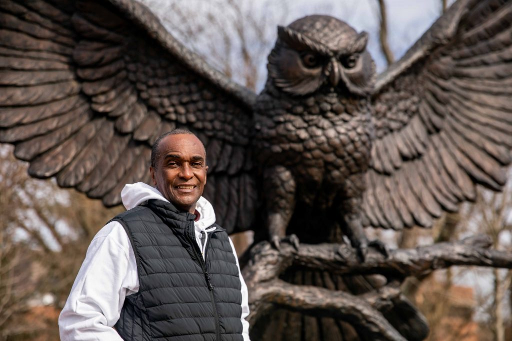 Eduardo standing in front of the Rowan owl statue.