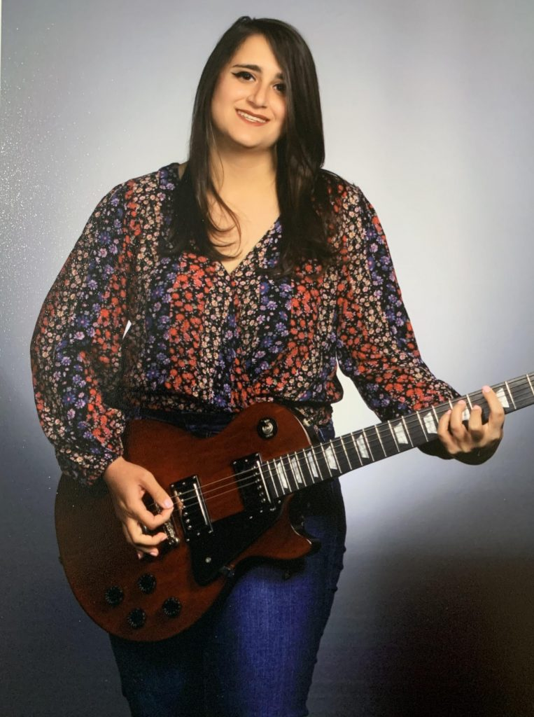 Kristina poses with a guitar.