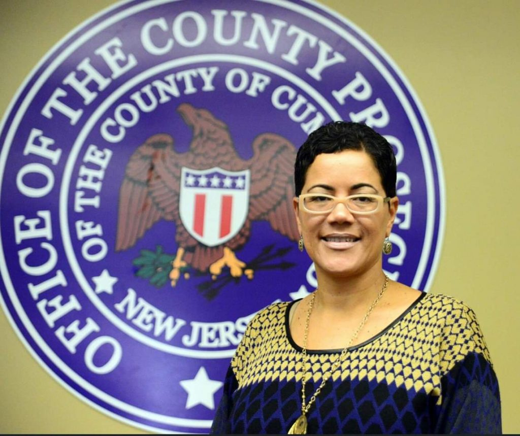 Jennifer in front of county prosecutor crest.