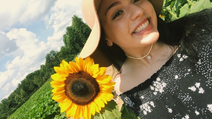 A selfie of Gianna holding a sunflower in a sunflower patch.
