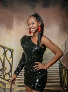 Mikiah posing for a photo wearing a black sequined dress and red earrings.