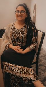 Kiran sitting and smiling for a photo while wearing a dress.