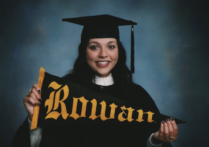 A portrait photo of Gianna wearing her high school cap and gown while holding a Rowan flag.