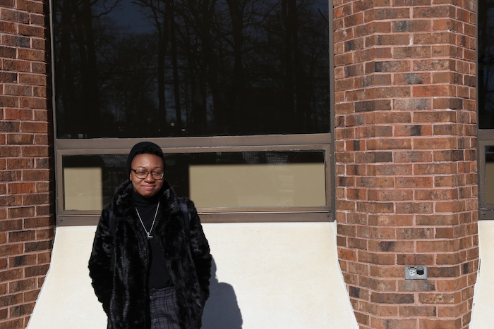 Daija posing outside the student center while wearing a furry black coat.