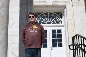 John standing on the steps of Bunce Hall while wearing a Rowan Psychology sweatshirt