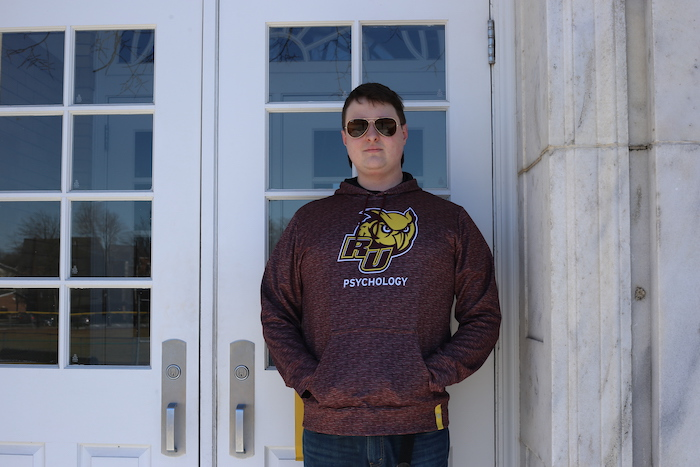 John standing against the door of Bunce while wearing sunglasses and a Rowan Psychology sweatshirt.
