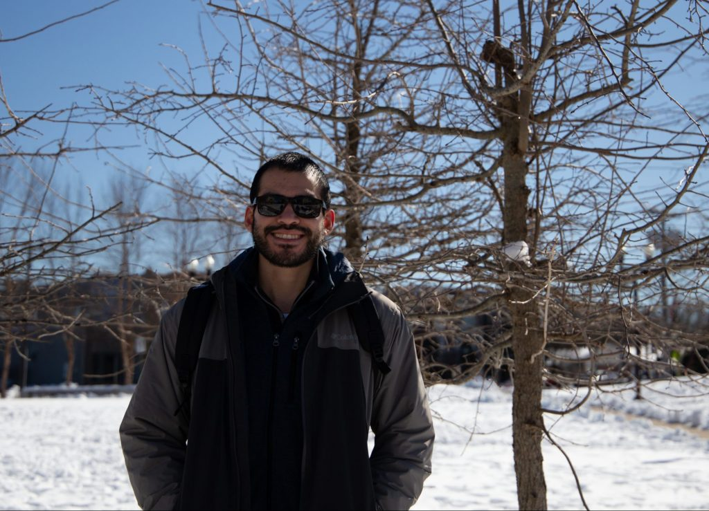 Jerico wears sunglasses, poses next to a bare tree on a snow-covered campus.