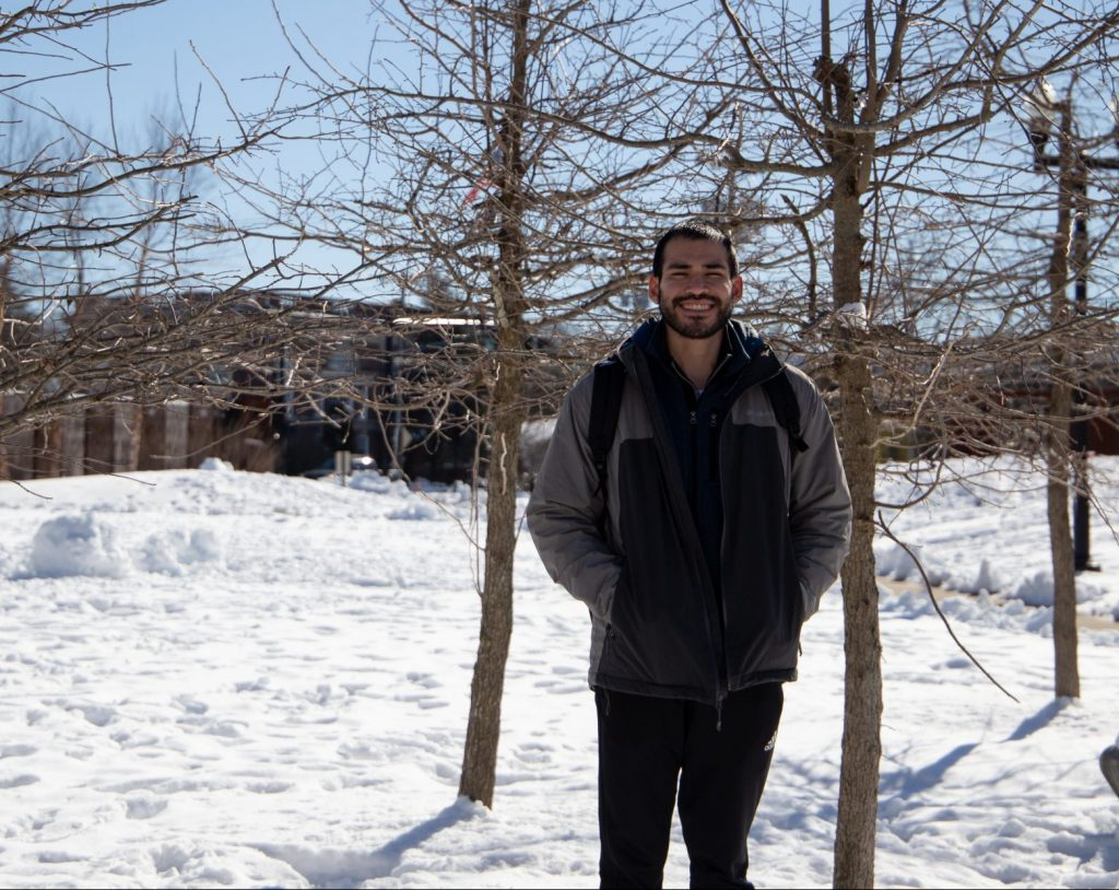 Jerico smiles, poses next to a tree outside on a snow-covered campus.