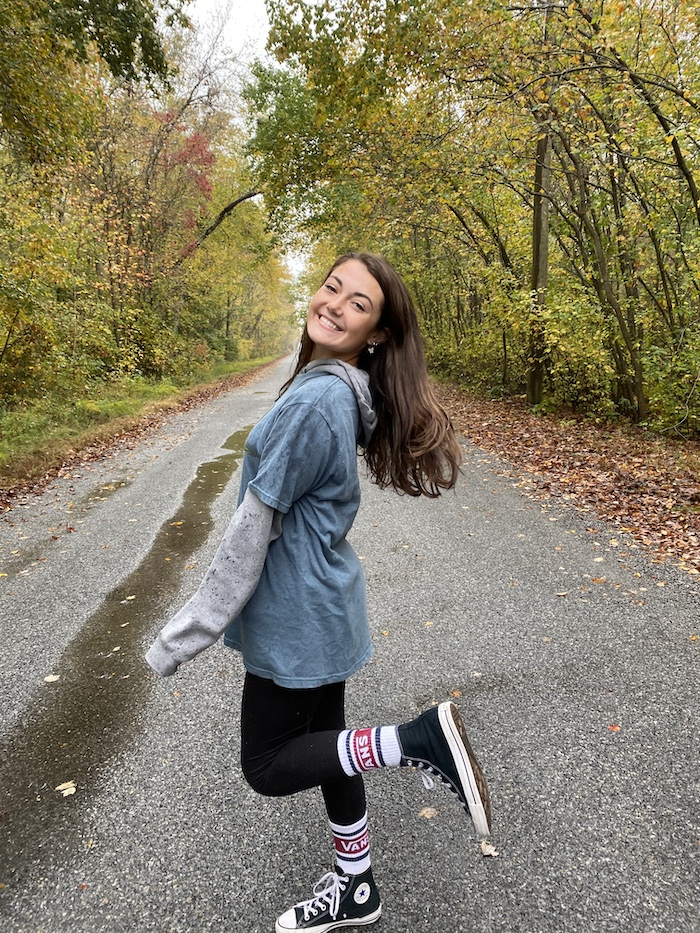 Kate smiling and lifting her leg for a photo while walking on a trail.