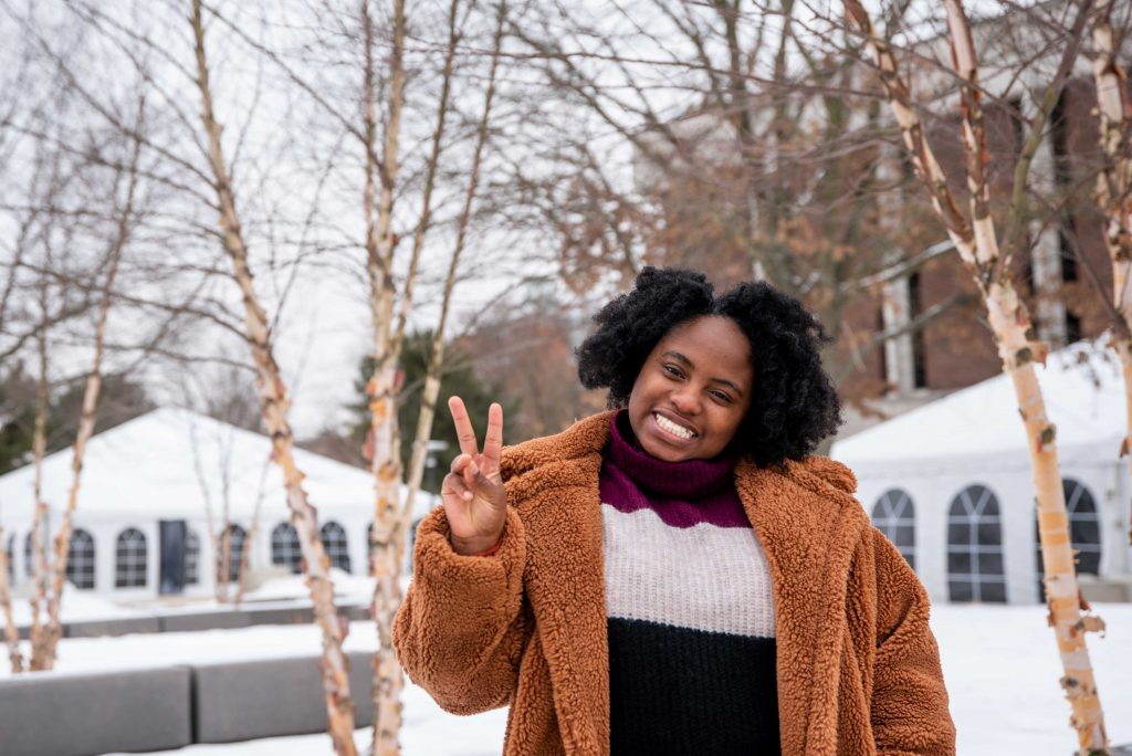LaDaysha standing near Robinson Hall holding up a peace sign with snow in the background.