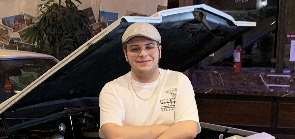 Richard wears a hat and stands next to a car in a supplied photo.