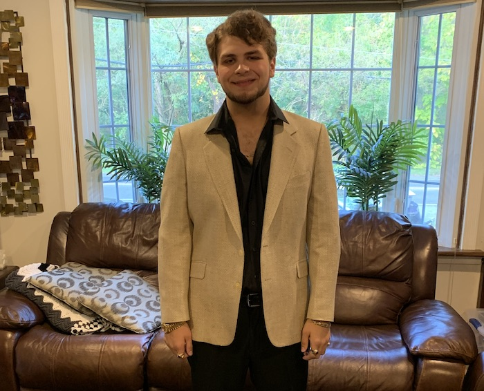 Richard smiling and wearing a tan suit jacket.