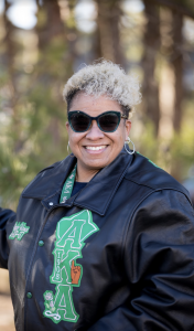 Kathleen smiling while wearing sunglasses and her sorority jacket.