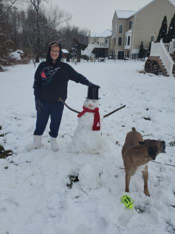 Zachary poses with a snowman.