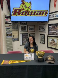 Kate signs with Rowan University wearing a Rowan shirt.