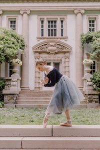 Paige in her ballet gear posing in front of an ornate building.