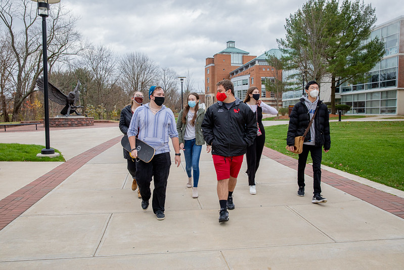 A group of Rowan students walk down campus.