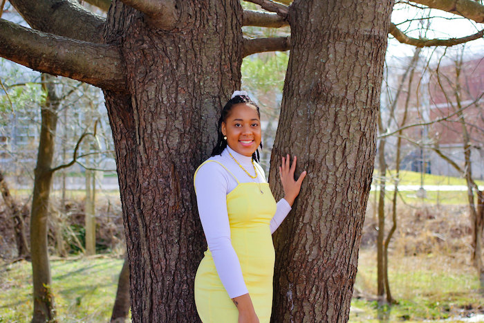 Ayanna wearing a yellow dress while posing against a tree.