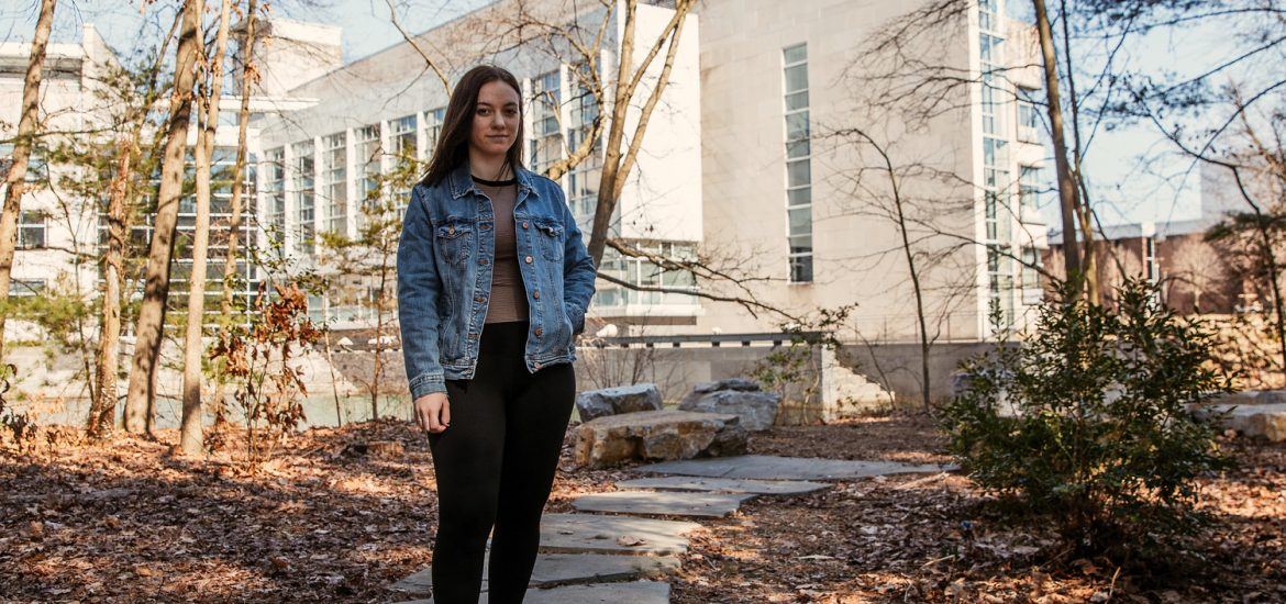 Lexi standing in a wooded area near Rowan Hall on campus.