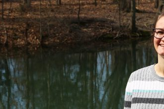 Allison stands and smiles next to a waterway on campus.